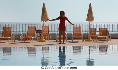 Girl does fitness exercises at pool near sea