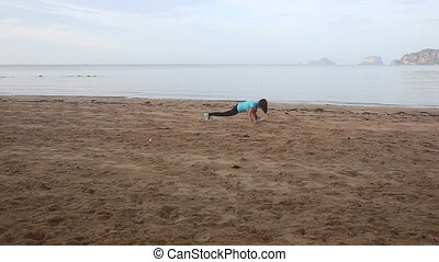 girl does morning exercises on beach at dawn against cliffs