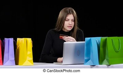 Girl does shopping online using her credit card and laptop. Black