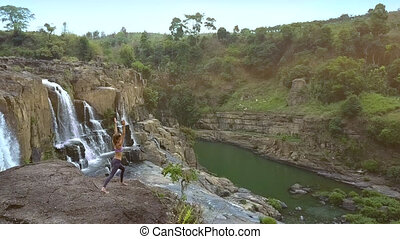 girl does yoga on rocky land against waterfall streaming from cliff
