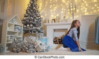 Girl doing acrobatics on the floor near the fireplace under the tree