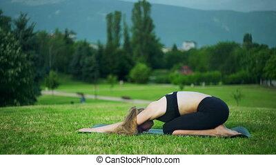 Girl doing basics yoga park. Morning sun on child pose