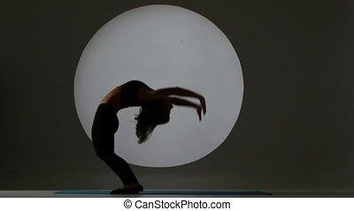 Girl doing bridge on the floor. Back light. Silhouette