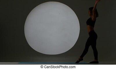 Girl doing cartwheel in a sport hall. Back light. Silhouette