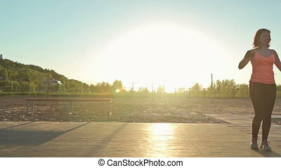 Girl doing cartwheel on a workout at scenic sunset.