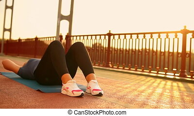 girl doing core exercises on the mat outdoor - young woman...