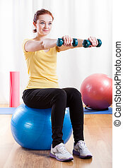 Girl doing excercise at the gym, vertical