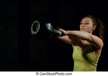 Girl doing exercise with weights in the gym.