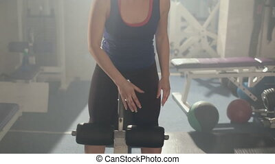 Girl doing exercises on a press in the gym