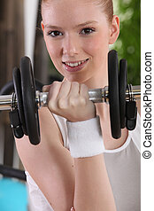 girl doing exercises with a dumbbell