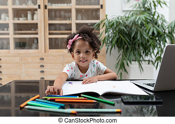 Girl doing her homework on table at home