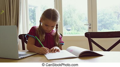 Girl doing homework at dining table in a comfortable home 4k