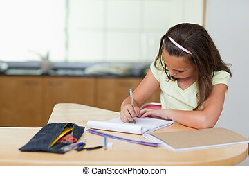 Girl doing homework in the kitchen