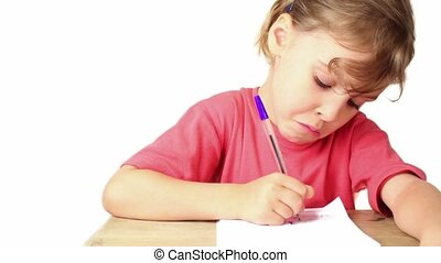 Girl doing homework, she writes pen on paper on table