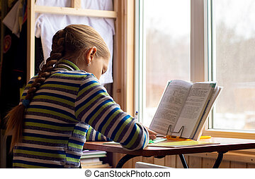 Girl doing homework sitting at the table by the window