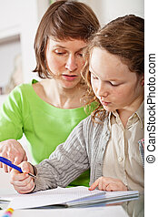 Girl doing homework with her mom - Mother helping her...