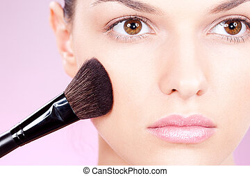 girl doing makeup with powder brush