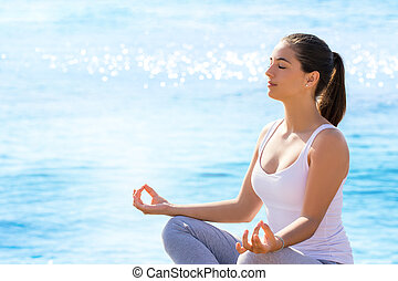 Girl doing meditation exercise at sea front.