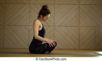 Girl doing neck warm-up exercise in sitting position. Young...