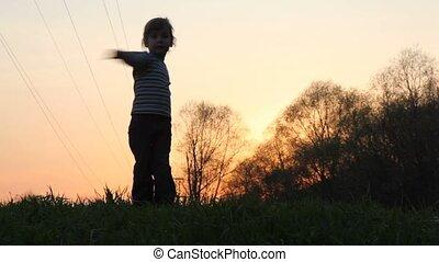 Girl doing physical training exercises on the sunset