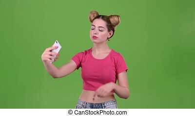 Girl doing selfie. Green screen. Slow motion