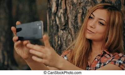 girl doing selfie on phone smartphone sitting in a tree outdoors slow motion