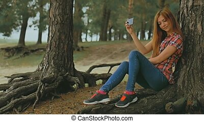 girl doing selfie on phone smartphone sitting in  tree slow motion outdoors
