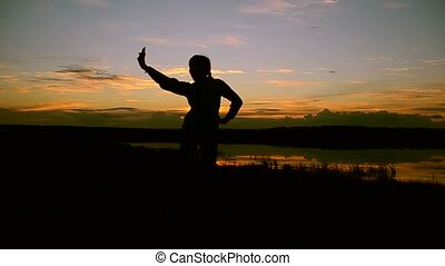 Girl doing selfie phone at sunset in water