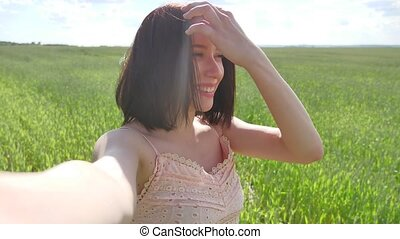 Girl doing selfie photographing herself on nature landscape...