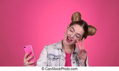 Girl doing selfie. Pink background. Slow motion - Girl does...