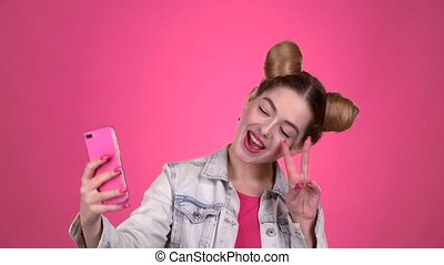 Girl doing selfie. Pink background