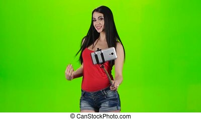 Girl doing selfie using a smartphone fixed on the monopod