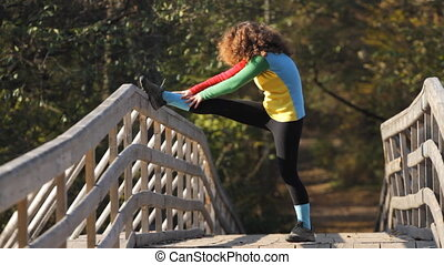 Girl doing stretching exercise on a bridge