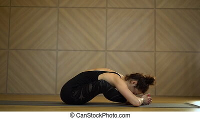 Girl doing stretching in sitting position. Young pretty...
