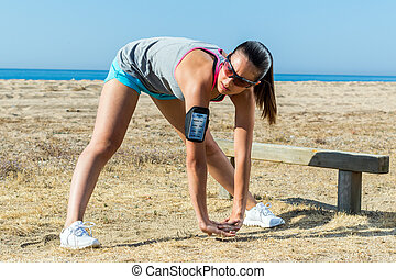 Girl doing warming up exercise outdoors.