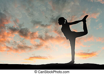 Girl doing yoga excercise at sunset.
