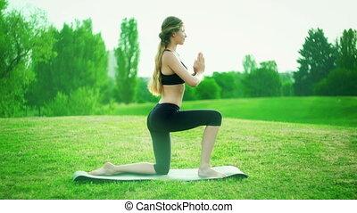 Girl doing yoga mist park. Morning kneeling salute sun pose...