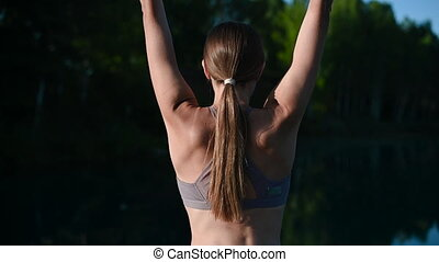 Girl doing yoga tree pose in nature. Girl yoga pose. Sports outdoors stretching on a fprest lake