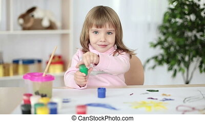 Girl drawing a green paint.