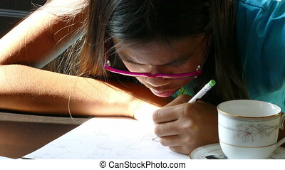 Girl Drawing A Picture - A cute 13 year old Asian girl...
