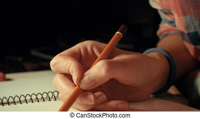 girl drawing a sketch with the pencil at her notepad