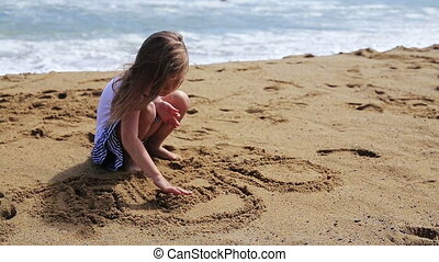 Girl drawing and jumps on  a sand beach.
