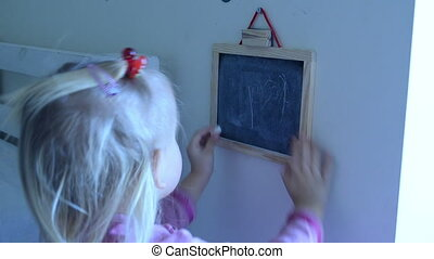 girl drawing art - girl rubbing her drawing on a black table...
