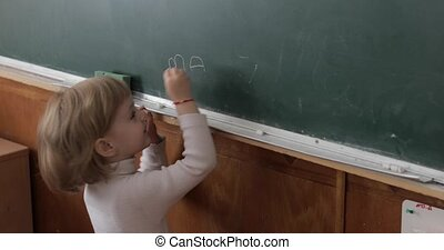 Girl drawing at blackboard using a chalk in classroom. Education process
