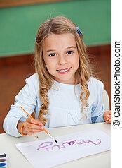 Girl Drawing At Desk In Kindergarten