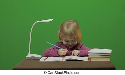 Girl drawing at the table. Education process in classroom....