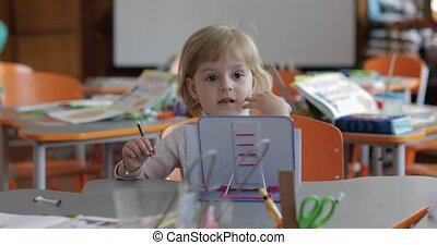 Girl drawing at the table in classroom. Education. Child sitting at a desk