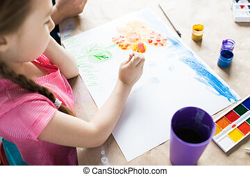 Girl drawing at the table