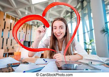 Girl drawing heart shape in the University class