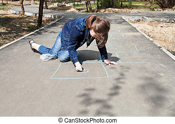 girl drawing hopscotch outdoors